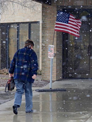 A voter enters Bethany Reformed Church under a sky of flurries, Tuesday, April 3, 2018, in Sheboygan, Wis.