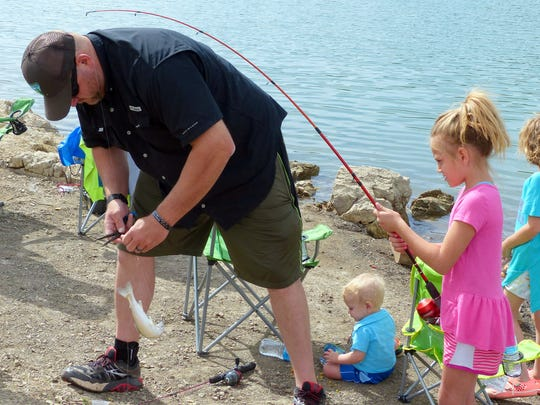 A father helps his daughter with her first catch of the day. Anglers can cast their baits at Grindstone Reservoir, Alto Lake and on the Rio Ruidoso.