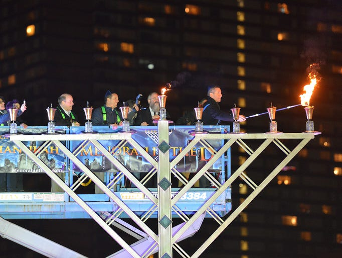 Dignitaries light a candle on the 26-foot menorah for
