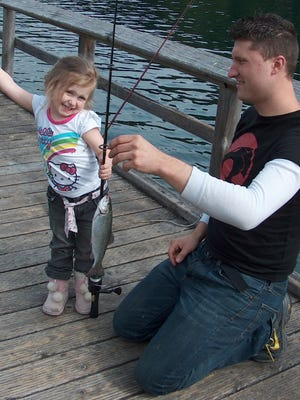 Ashley Dawn Neal poses triumphantly as dad David holds up a fish that she caught during a recent Free Fishing Weekend event at Hoover Campground at Detroit Lake.