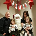 Brad Giesting, left, and his wife Annie on a recent visit with Santa Claus with their daughters, Hailey, 5, and Lucy, who turns 4 on Dec. 27.
