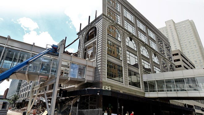 In this composite image the Younkers building is shown at the intersection of 7th and Walnut Streets in 2005 shortly before the landmark department store closed (right) and on June 25, 2014, about three months after it was destroyed by fire. (left)
