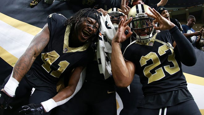 Alvin Kamara #41 of the New Orleans Saints, Marshon Lattimore #23 and Michael Thomas #13 celebrate after a game against the Atlanta Falcons at the Mercedes-Benz Superdome on December 24, 2017 in New Orleans, Louisiana.