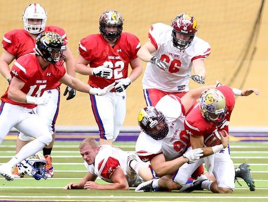 North Squad's Kyler Schott tackles South Squad quarterback