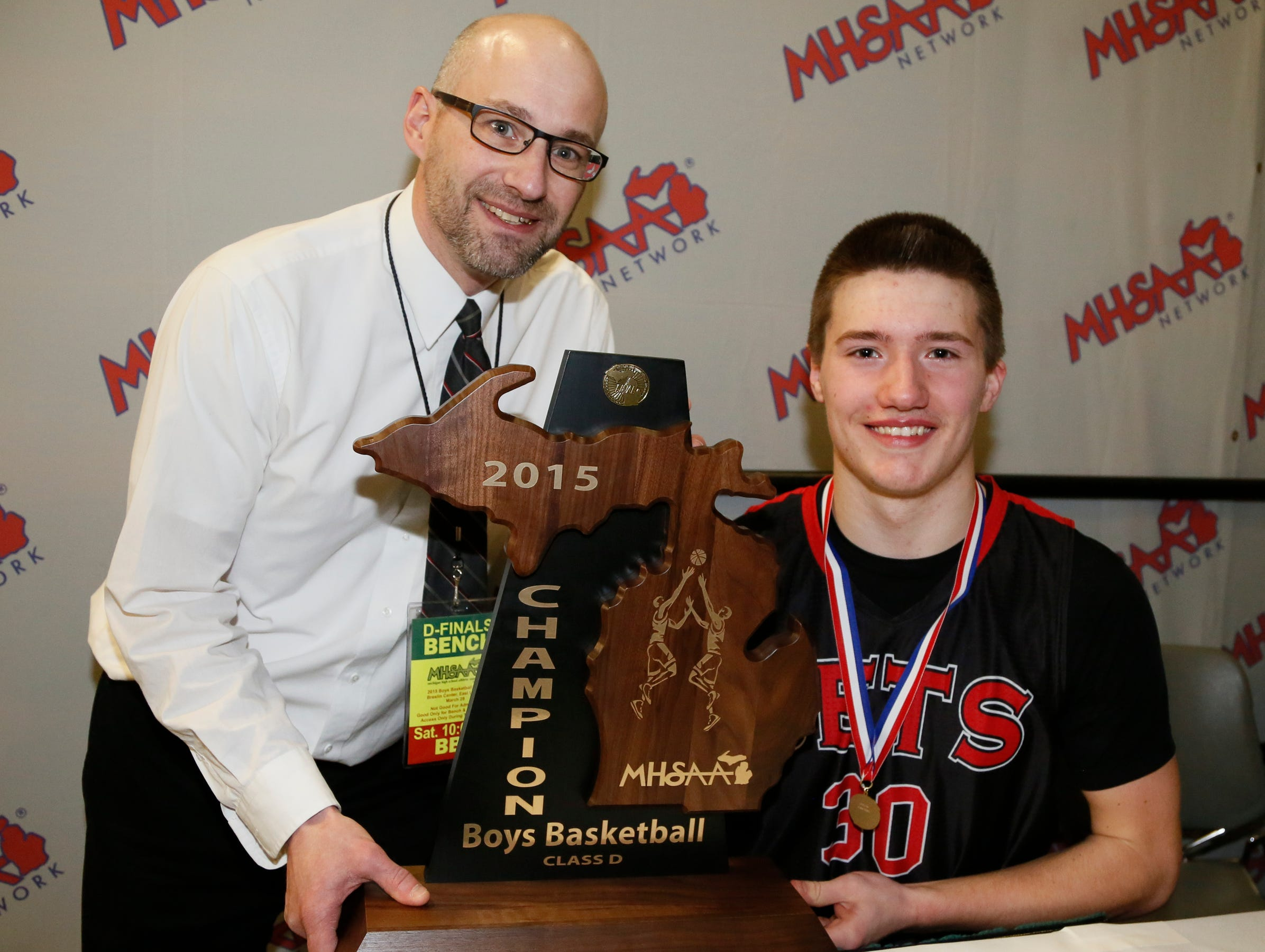 Powers North Central's Jason Whitens, with the Class D championship trophy on Saturday, March 28, 2015 in East Lansing, poses with his father, Gerald Whitens, who was on Powers North Central's championship team in 1984.