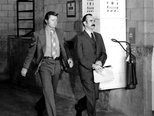 G. Gordon Liddy (right), handcuffed and in the custody