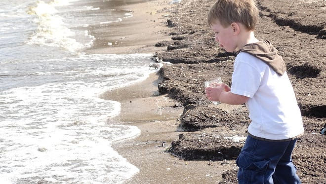 """Andrew """"Finn"""" Czerwinski, 2, of Port Clinton pours a jar of water into Lake Erie on Sunday at Port Clinton's city beach as part of a healing waters ceremony organized by residents Toni Garrett and Carol Clemons."""