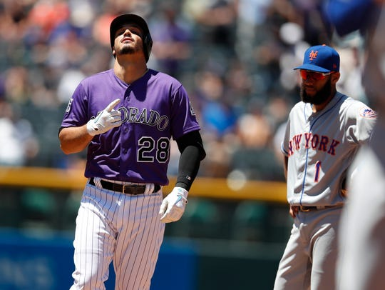 Colorado Rockies' Nolan Arenado, left, gestures as