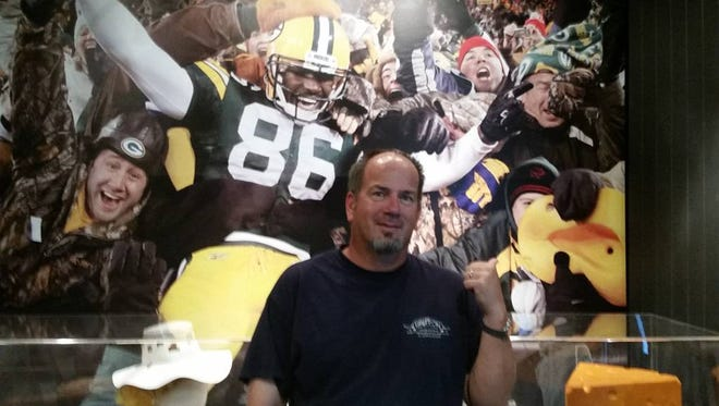 Doug Junk at the Pro Football Hall of Fame in Canton, Ohio standing in front of a photo of him, his son Augie and former Packer player Donald Lee during a Lambeau Leap in 2011.