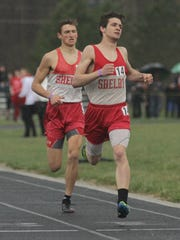 Shelby's Sam Logan overtakes teammate Blake Lucius to win the 800 meters at the Mehock Relays on April 14, 2018.