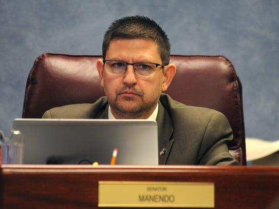 Senator Mark Manendo listens to a speaker during a