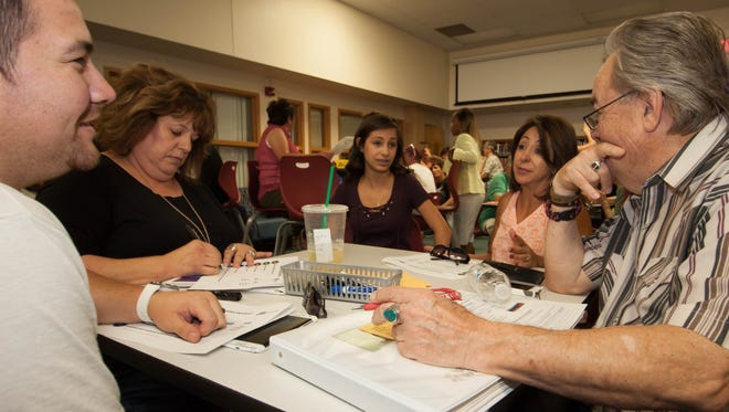 Community members — including, from left, Andrew Montoya, Mary Parr-Sanchez, Megan Apodaca, Melissa Apodaca, and Mike Milam — break into groups Monday, June 16, 2016, to discuss factors related to Lynn Middle School becoming the first community school in Las Cruces. Community schools are aimed at mitigating the impacts of poverty on children, according to Tim Hand, chief of staff and director of assessment, analysis and research for Las Cruces Public Schools.