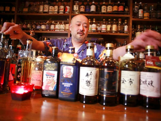 "In this March 10, 2017 photo, shot bar Zoetrope owner and bartender Atsushi Horigami adjusts the bottles of Japan-made whisky at his bar in Tokyo. Zoetrope, a tiny bar in a dingy building in a Tokyo backstreet, is famous among whisky lovers for specializing in Japanese whisky. ""Japanese whisky has an unpredictability that makes it fun, and the highly skillful Japanese blenders have created a subtle taste with an impeccable balance,"" said Horigami."