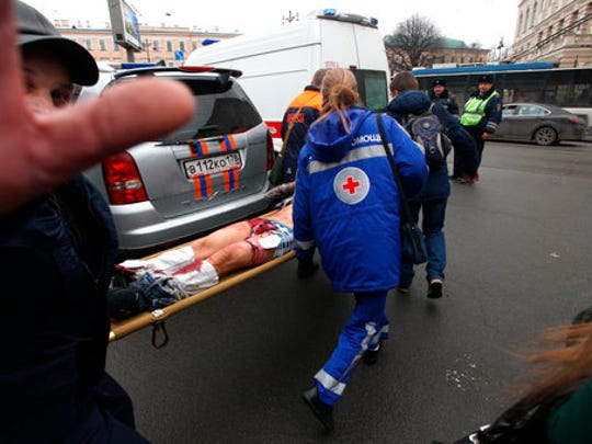Paramedics carrie a subway blast victim into an ambulance after explosion at Tekhnologichesky Institut subway station in St.Petersburg, Russia, Monday, April 3, 2017. The subway in the Russian city of St. Petersburg is reporting that there are fatalities and several people have been injured in an explosion on a subway train.