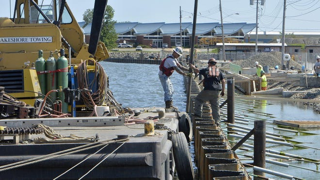 Lakeshore Towing construction workers on Aug. 14 help build a seawall near Dobbins Landing. The Erie-based boat towing and marine construction company has encountered the busiest summer in its 32-year history.