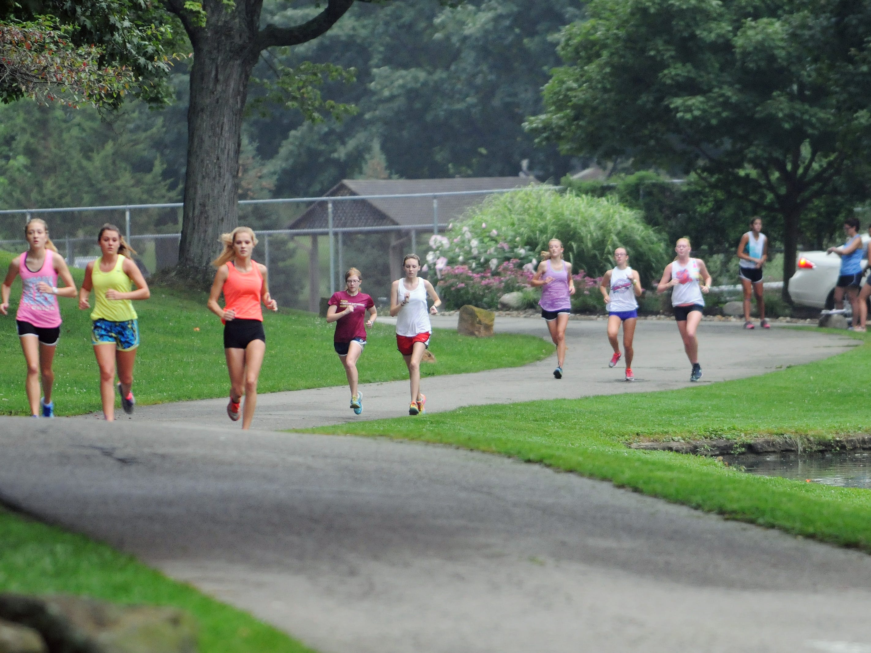 The Lancaster High School girls cross country team runs during practice Aug. 12 at Rising Park in Lancaster.