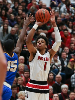 New Albany's Romeo Langford (1) shoots against Carmel's Jalen Whack (15) during their game at New Albany High School.  New Albany edged Carmel 55-52.Dec. 20, 2016