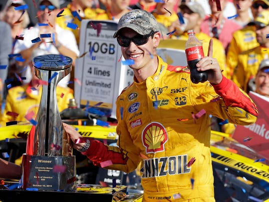 Joey Logano poses with the trophy in Victory Lane after winning the NASCAR Sprint Cup series auto race at Charlotte Motor Speedway in Concord, N.C., Sunday, Oct. 11, 2015. (AP Photo/Terry Renna)