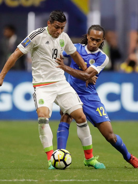 Mexico's Angel Sepulveda (19) ad Curacao's Shanon Carmelia (12) battle for control of the ball during a CONCACAF Gold Cup soccer match in San Antonio, Sunday, July 16, 2017. (AP Photo/Eric Gay)