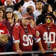 Cardinals fans (right) show their emotions after the 49ers kicked a game-winning field goal to win 23-20 at University of Phoenix Stadium in Glendale December 29, 2013.