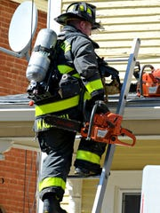 A firefighter carries a chainsaw as he climbs to the