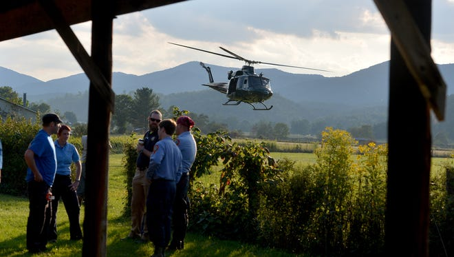 """A helicopter takes off near search team members who wait for their turn to join the search for a missing pilot at the mobile command center at the Deerfield Volunteer Fire Department on Wednesday, August 27, 2014. An F15C """"Eagle"""" fighter jet crashed into a mountain near Elliot Knob in Augusta County on Wednesday morning."""