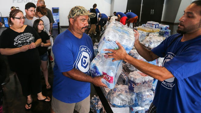 Volunteers picks up supplies for residents affected by Hurricane Harvey Monday, Aug. 28, 2017, at Church Unlimited in Corpus Christi.