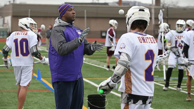 East United head coach Sean Banks directs the squad through warm up drills before their game against Aquinas at East High School Wednesday, April 18, 2018.   East United is the first varsity lacrosse team based in the City of Rochester.