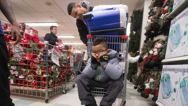 Dylan Morales pouts while shopping on Thursday, Nov. 27, 2014, with his father Rigoberto at Kmart on New York's 34th Street.