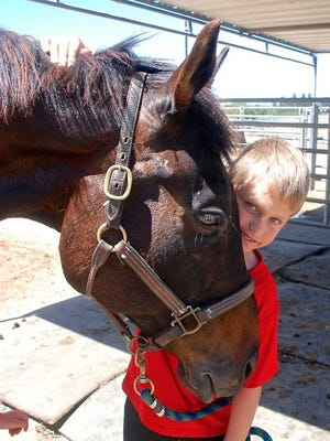 Owen Alderson, 9, with Rocky, 21, a former hunter-jumper, now one of five horses in the Hope, Horses & Kids program.