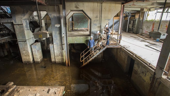 Tad Cooke, (from left) Charlie Tipper and Erick Crockenberg tour a flooded portion of the Moran plant in Burlington on July 21, 2015.