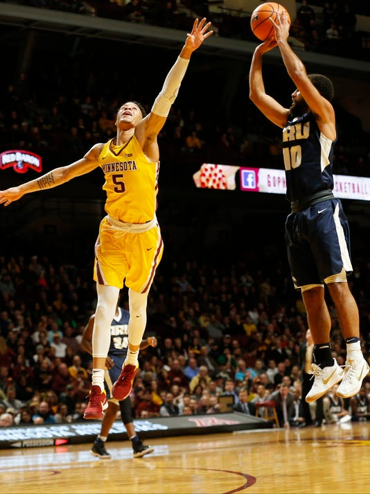 Oral Roberts' Sam Kearns, right, shoots as Minnesota's Amir Coffey defends in the first half of an NCAA college basketball game Thursday, Dec. 21, 2017, in Minneapolis. (AP Photo/Jim Mone)