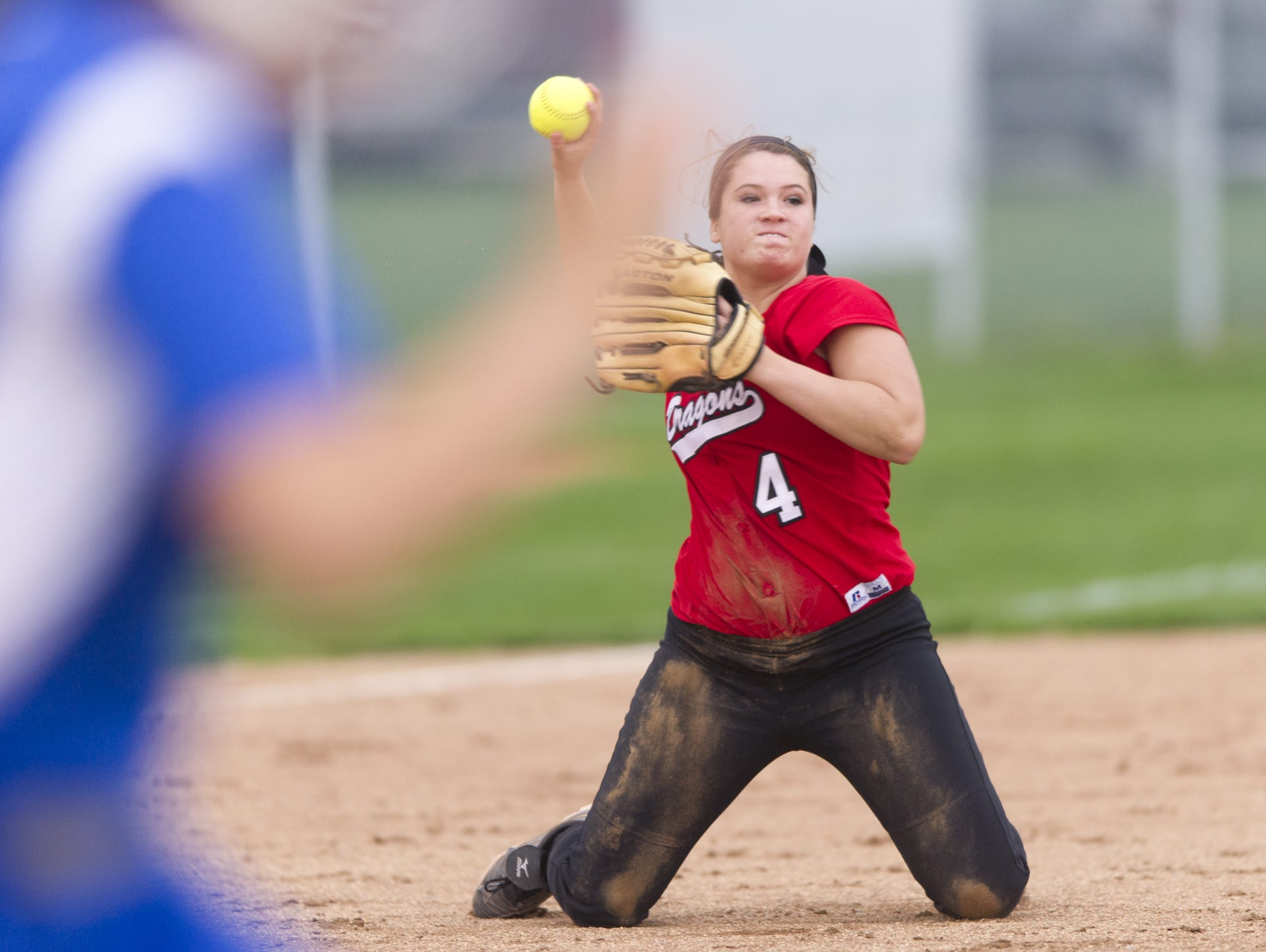FILE -- New Palestine High School junior Issy Hoyt (4) makes the throw from her knees at third base to get the runner out at first. Hamilton Southeastern High School hosted New Palestine High School in varsity softball action, Thursday, April 16, 2015. New Palestine won 2-0, in 9 innings.