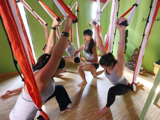 Aeroyoga instructor Nashyelli Elena Hernandez leads a small group of women who use a hammock-like apparatus in class Friday.