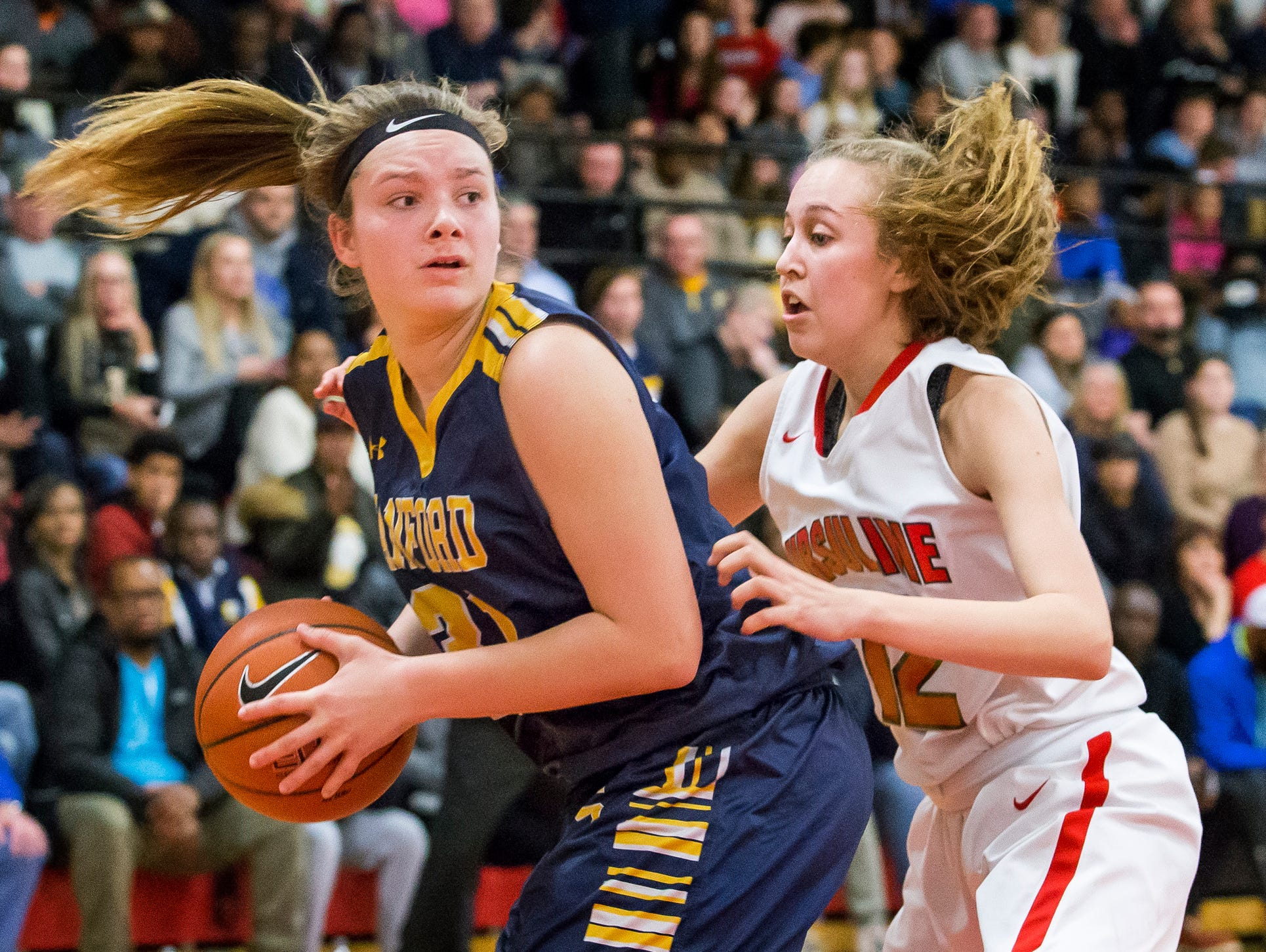 Sanford's Allie Kubek looks for room to pass as she's defended by Ursuline's Olivia Mason (right) in the second half of Ursuline's 50-40 win over Sanford at Ursuline Academy on Thursday night.
