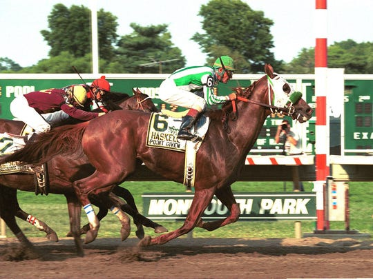 Point Given, ridden by Gary Stevens, hits the wire ahead of  Touch Tone (inside) and  Burning Roma to win the  $1,500,000 Haskell Invitational at Monmouoth Park.