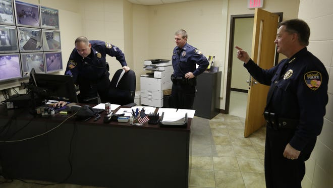 Oshkosh Police Chief Scott Greuel, right, explains how officers keep an eye on security from the Patrol Operations Center inside the Public Safety Building. Greuel retired Jan. 8, 2016, after three decades of serving the Oshkosh community.