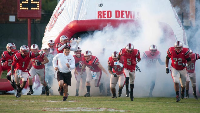 Jeffersonville Red Devils head football coach Lonnie Oldham (in white shirt) takes to the field with his team as they prepare to take on the New Albany Bulldogs on Jeff's home field. 03 October 2014