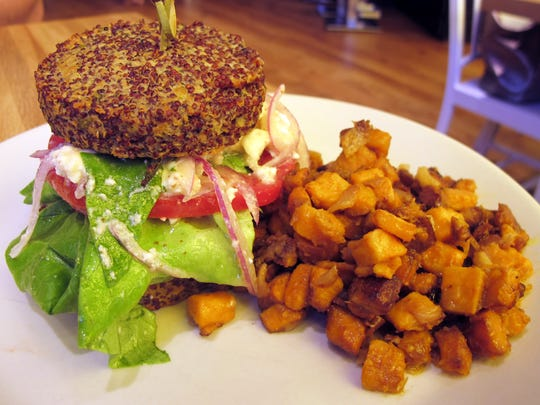 Inside Out Quinoa Burger with hummus, tzatziki, tomato, cucumber, red onion, avocado and feta with a side of sweet potato hash at True Food Kitchen in Naples' Waterside Shops.