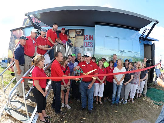 A group gathers Wednesday for a ribbon-cutting ceremony to christen the Spudmobile at the Wisconsin Farm Technology Days in Portage County.