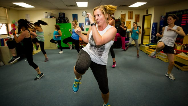 Mindy Tapia leads a class of nine other East Picacho Elementary staff members during a cardio kickboxing class at East Picacho Elementary at the end of the school day.