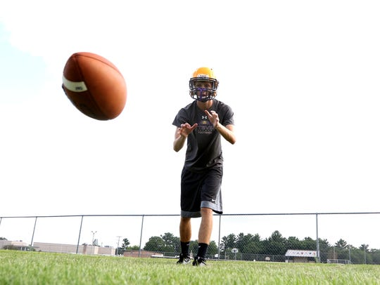 A Pittsville High football player catches a low pass