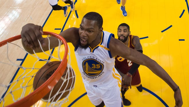 Golden State Warriors forward Kevin Durant (35) dunks the basketball against Cleveland Cavaliers guard Kyrie Irving (2) during the first half at Oracle Arena.
