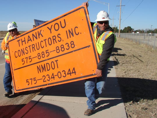 Edward Granger, left, and Jon Franklin carry the sign that will be placed on U.S. 285 indicating the start of a $2.5 million roadway rehabilitation project.