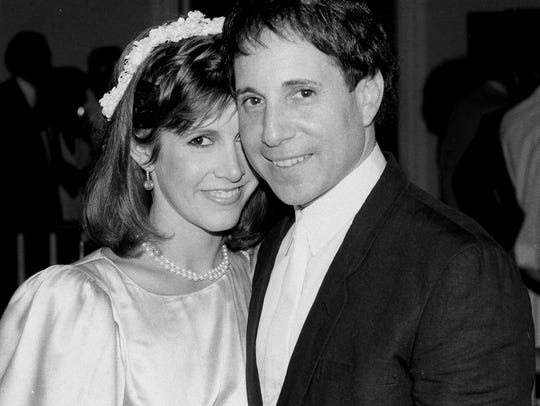 Carrie Fisher and singer Paul Simon stand together