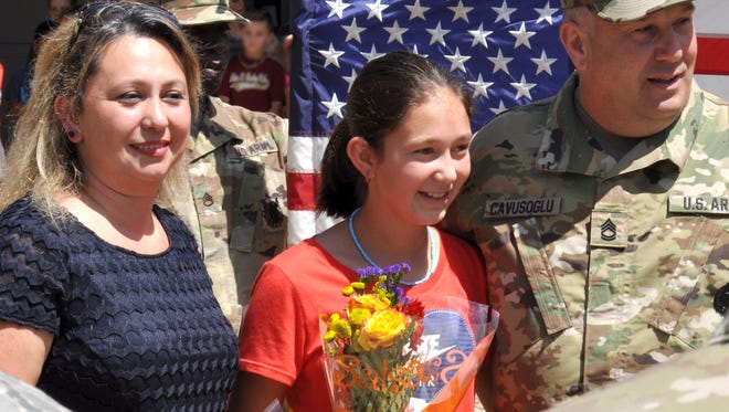 Mrs. Serpil Cavusoglu on the left in navy, his daughter Dilahan, a fifth grader at FSUS, is in the center in red and newly promoted Sergeant First Class Mehmet Cavusoglu is on the right.