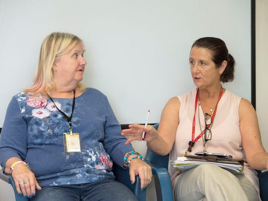 "A client (left) speaks to Marie Verna about how journaling, tai chi and chair yoga empowers her. Calling stigma ""the biggest issue in mental health,"" Verna said it creates barriers to people trying to regain their lives."