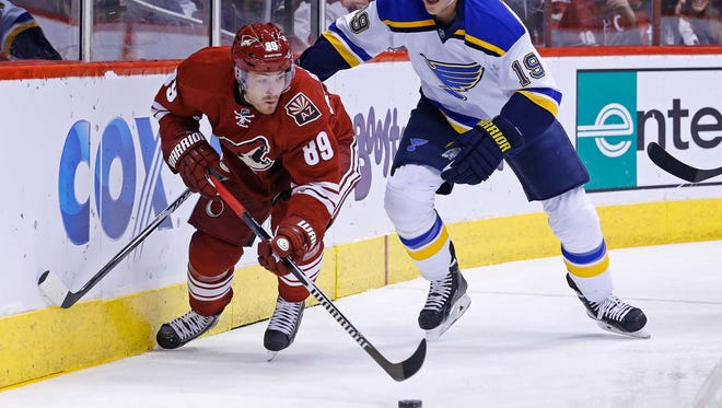 Arizona Coyoteswing Mikkel Boedker (89) controls the puck with St. Louis Blues defenseman Jay Bouwmeester (19) in tow during the first period on Tuesday, Jan. 6, 2015, in Glendale.