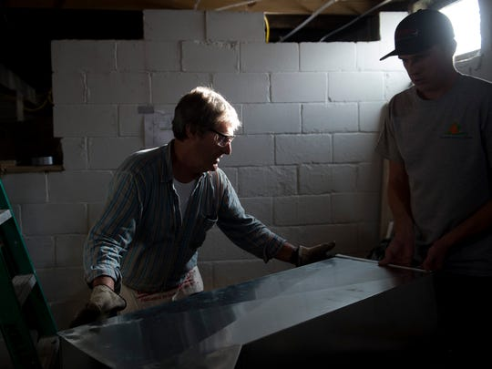 Ivy Tech's Heating Ventilation and Air Conditioning students Jeff Hackett, left, and David Hall, right, move a piece of ductwork while working on the HVAC system in one of Community One's homes at 610 Madison Street in Evansville, Ind., on Thursday, Oct. 19, 2017. Students in Merle's HVAC class are working on this home as part of a service learning project in conjunction with Community One, a nonprofit group that addresses housing restoration and community development needs in Evansville.