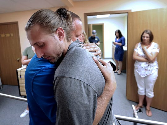 After standing for the first time in two months, Collin VanderGalien embraces his father, Bill, during an appointment fitting him with new prosthetic legs at Sisson Mobility Restoration Center, Inc. in Monona, Wis. VanderGalien lost both of his legs in an explosion at the Didion Milling Plant in Cambria, Wis. in May.